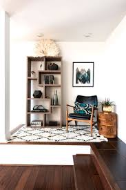Bright white reading nook with bookshelf, chair and printed rug