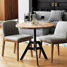 smooth round of solid sustainable acacia wood lifts and lowers from coffee table to kitchen bistro with a simple