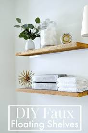 diy faux floating shelves made of barn wood hanging on a bathroom wall