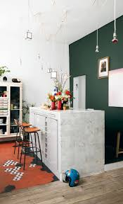 Green accent wall in kitchen with marble island and bar stools