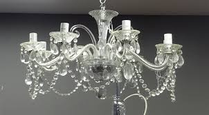 eight branch clear glass chandelier with cut glass drops scrolled arms and the branches having