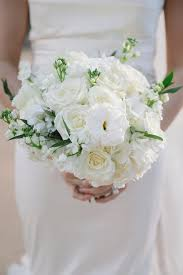 gorgeous winter wedding bouquet with white flowers and greenery by garden gate in dallas texas photo by evan win photography