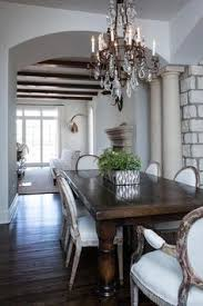 french dining room boasts a crystal chandelier illuminating a dark wood dining table lined with gray