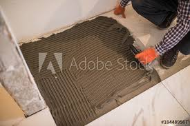 laying ceramic tiles troweling mortar onto a concrete floor in preparation for laying white floor