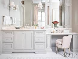 pink and gray master bathroom features light gray walls framing a light gray washstand accented with glass knobs and pink marble countertops placed beneath
