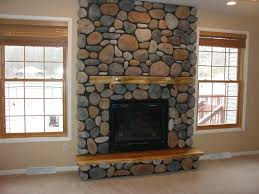 adirondack style fireplace with river rock cultured stone and wood hearth and mantle