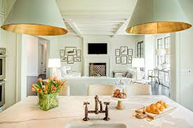 a marble top island is fitted with a sink and a burnished brass deck mount faucet illuminated by goodman hanging lamps which overlooks the living room