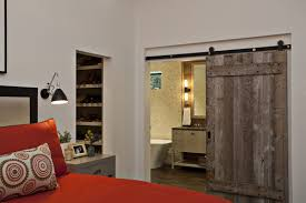 a barn door on a sliding track can be used to divide a bedroom and an ensuite bathroom in country style the clearance space under the door that stops it
