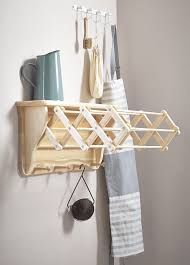 the wall mounted laundry drying rack in wood with the clothes airering arms inside