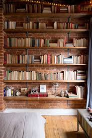 Books resting against a brick wall make this room look warm and welcoming!