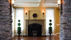 fireplace windows. fireplace framed with topiary and sheer curtained windows. windows o