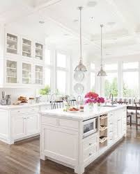 All White Kitchen With White Tiles, White Cabinets, Marble Counters, And  Tall