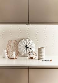 hexagonal white tile backsplash white grout brown cabinets white countertop geometrical candle holders