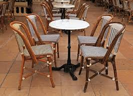 beautiful french outdoor cafe with small round tables and wicker chairs photo by felker