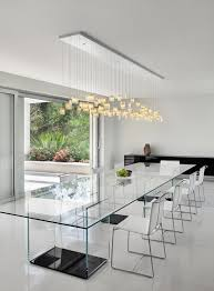 an ethereal all glass dining table with dark bases and neutral chairs a pendant