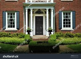 red brick house with black shutters and green shrubs with front door flanked by pillars and