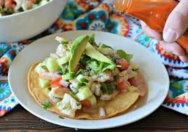 adding hot sauce to ceviche