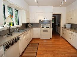 kitchen with track lighting. Cottage Kitchen With Corian, Flat Panel Cabinets, U-shaped, Track Lighting, Lighting