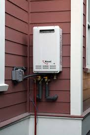 a whole house tankless natural gas water heater installed outdoors showing its