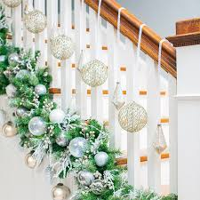 Christmas staircase with garland at railing base, with silver and white  ornaments inserted; white