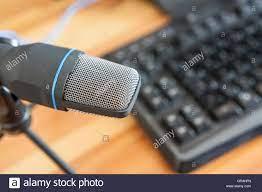 Professionelles Mikrofon mit Computer-Tastatur über hölzerne Desktop-Oberfläche.  Podcast-Konzept Stockfotografie - Alamy