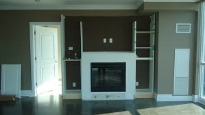 white concrete frame fireplace combined with white glaze wooden tall narrow shelving unit attched on brown