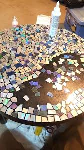 diy mosaic table he cuts his old collection into pieces then he grabs the glue making outdoor mosaic table top