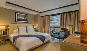 A Suite Bedroom With Beige Walls And A King Size Bed With White Dressings  And A
