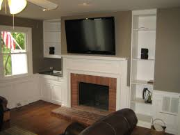 traditional exposed red bricks wall fire place with white painted f mantel shelf and mounted wide screen tv