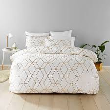 chic white bedding with geometric gold prints for an elegant and glam bedroom