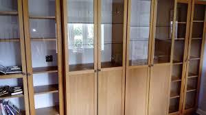 double ikea oak veneer billy bookcase with glass shelves and half glass doors