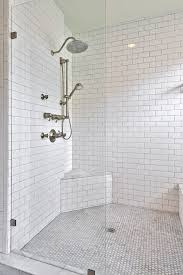 shower partition alongside dual shower heads framed by a floor to ceiling subway tiled interior with gray grout including a built in corner shower seat