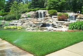 layered stone waterfall in a corner of a backyard backyard landscaping ideas rocks