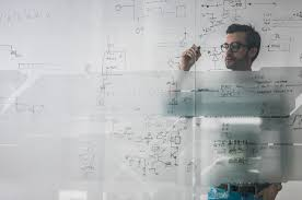 male engineer working on new ideas and writing diagram on glass wall