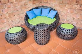 oldbrick furniture. Sofa Furniture Weave Rattan Stick Chair With Blue Pillows On Orange Tile And Old Brick Wall Oldbrick T