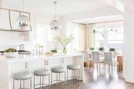 pendants illuminate a white kitchen island fitted with cabinets topped with white quartz lined with backless dove gray leather swivel counter stools