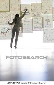 businesswoman writing on paper on glass wall
