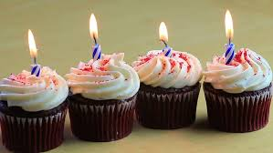 Four Chocolate Birthday Cupcakes With Blue Candles Burning