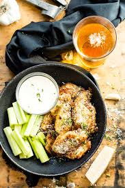 easy baked en wings with parmesan and garlic sauce in a black bowl with celery