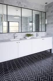 black herringbone floor tiles accented with white grout lead to a dual washstand fitted with white flat front cabinets donning matte black hardware and a