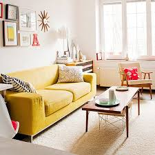yellow sofa / off white walls / Relaxed modern living room with mid-century  modern decor. Mustard yellow sofa stands out in a white room with wood  accents!