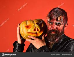 devil or monster with october decorations man wearing scary makeup holds pumpkin on red background party concept demon with horns and calm face