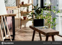interior artist studio potted plants painting supplies laptop blank screen stock photo