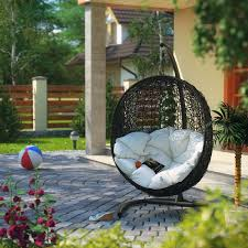 round black wicker hanging swing chair with white cushion and black metal curved pedestal comfy