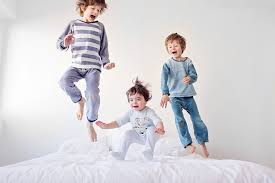 natural light photo of kids jumping on bed by French photographer Lisa  Tichane of Tout Petit