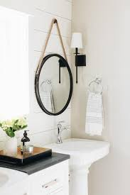 beside a window a rope hanging mirror is hung from a white shiplap wall over a white pedestal sink finished with a chrome faucet