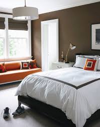 bedroom with chocolate brown walls paint color mahogany bamboo roman shades orange bench with nailhead trim black wingback bed white hotel bedding