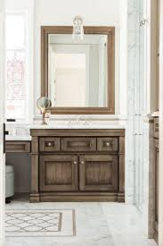 brown bathroom furniture. gray and brown bathroom features a washstand topped with white marble under beveled vanity mirror alongside tiled floor inset furniture
