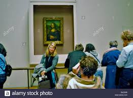 paris france interior louvre museum italian paintings exhibit tourists looking at mona lisa painting by leonardo da vinci