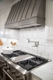 Fixer Upper - Gorgeous kitchen with crisp white cabinets paired with  carrera marble countertops and large subway tiled backsplash flank stained  wood hood ...